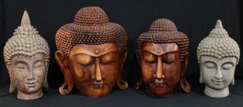 An Indonesian carved wooden bust of The Buddha, 35cm; another similar smaller, 32cm; another