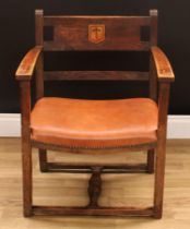 An Arts & Crafts ecclesiastical open armchair, curved cresting rail centred by a shield shaped