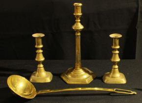 A George III brass candlestick; another pair, Victorian; a large brass ladle (4)