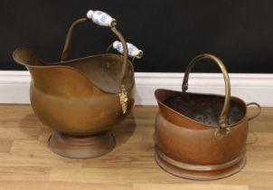 A brass helmet shaped coal scuttle with Delft blue ceramic handles; a copper coal scuttle (2)