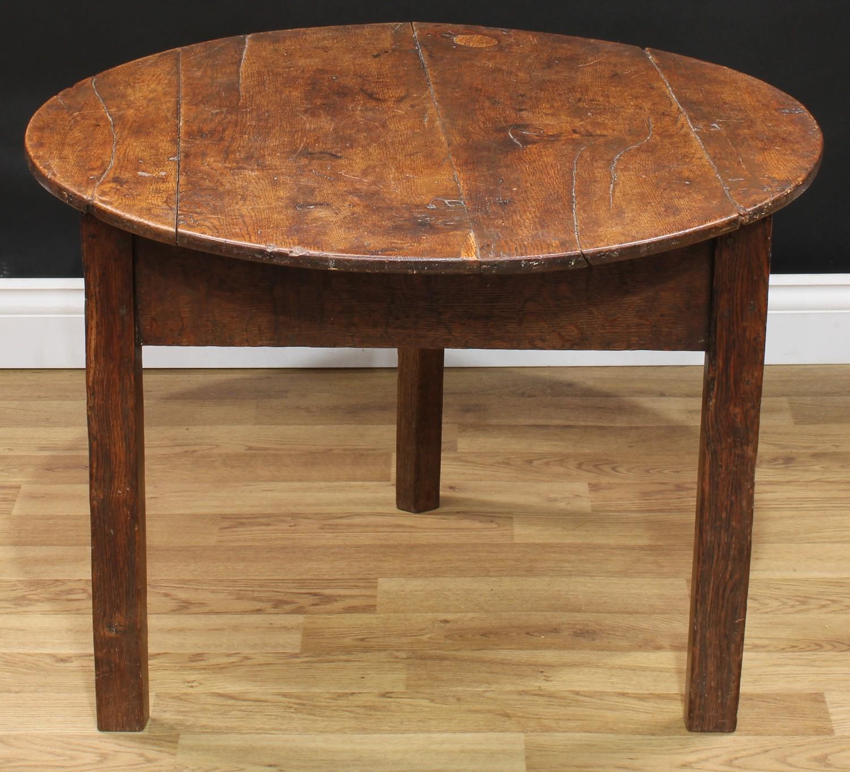 A 19th century oak cricket table, circular top, chamfered legs, 55.5cm high (reduced), 77cm diameter