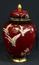 A Carlton Ware rouge royale lustre vase and cover, decorated with ducks and irises, 28cm high