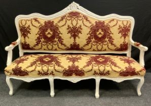 A Victorian painted three-seat salon sofa, shaped and carved cresting rail, stuffed over upholstery,