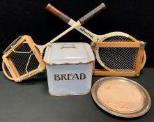 An early 20th century enamelled bread bin; an E.P.N.S. mounted bread board; a Slazenger tennis