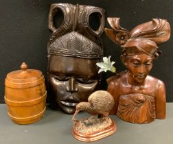 An African hardwood figure; a similar mask; a turned wooden tea caddy; a copper kiwi