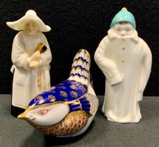 A Royal Worcester candle snuffer as a Nun; another, child in large winter coat, black, back stamp; a