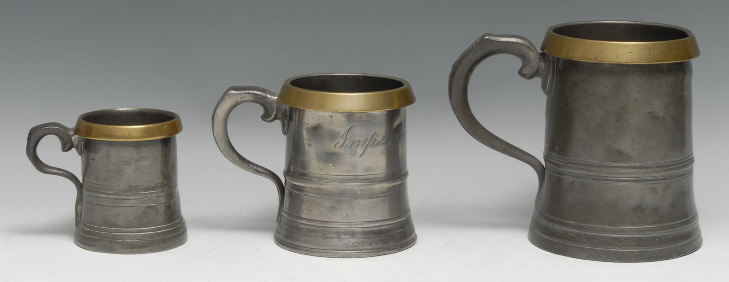 Three 19th century brass-mounted pewter tavern measures, the largest 15cm high, [3]
