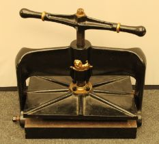 A 19th century cast iron book press, the frame in relief and picked out in gilt with a recumbent