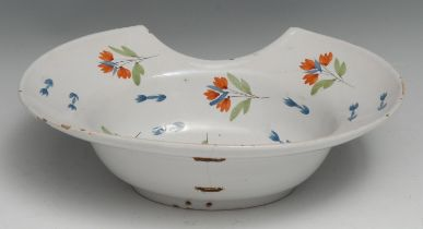 A 19th century French faience barber's blood-letting bowl, painted with scattered sprigs in