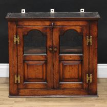 An oak wall hanging cabinet, shallow cornice above a pair of partially glazed doors, the lower