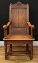 A 19th century oak Wainscot armchair, of pegged construction, shaped cresting rail centred by a