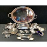 A pair of sliver plated twin handled entree dishes and covers; another, navette; a bottle stand;