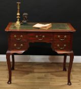 A George II Revival mahogany kneehole desk, shaped rectangular top with inset tooled and gilt