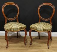 A pair of Victorian walnut balloon back side chairs, each cresting and mid rail carved with
