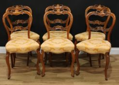 A set of six Victorian walnut balloon back dining chairs, each shaped cresting and mid rail carved