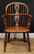 A 19th century yew and elm Windsor elbow chair, low hoop back, shaped and pierced splat, curved