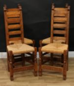 A set of four Rupert Griffiths Monastic Woodcraft oak ladder back dining chairs, rush seats,