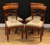 A set of four William IV mahogany dining chairs, each with a curved cresting rail above a shaped and