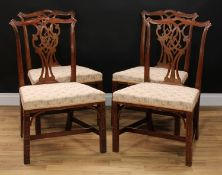 A set of four Chippendale Revival mahogany dining chairs, of broad proportions, each with a cupid'