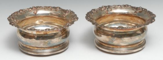 A pair of Regency Old Sheffield Plate wine coasters, of deep proportions, fruiting vine borders,