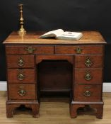 A George III oak kneehole desk, slightly oversailing rectangular top with moulded edge above an