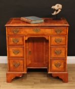 A George II Revival walnut kneehole desk, rectangular top with moulded edge above a long frieze
