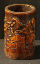 A Chinese bamboo bitong brush pot, carved in relief with a monumental landscape, 17.5cm high
