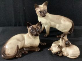 A Beswick model of a Siamese cat, standing; another, recumbent; a model of two kittens (3)