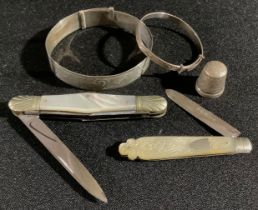 A silver and mother-of-pearl fruit knife; a pen knife; a silver thimble; silver bangles; etc