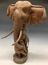 A carved hardwood African elephant family group, mother with three entwined calves, 63cm high (