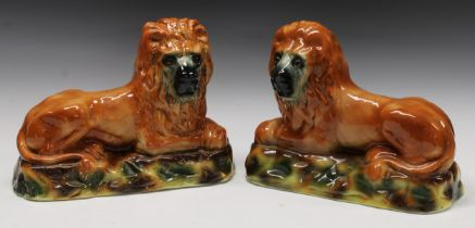 A pair of 19th century Staffordshire mantel lions, each with glass eyes and painted in tones of