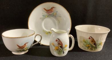 A Royal Worcester tea cup and saucer, by W Powell, signed, painted with a wren, printed mark in