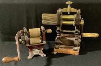 A 19th century brass crimping iron, cast iron stand; another, table top roller (2)