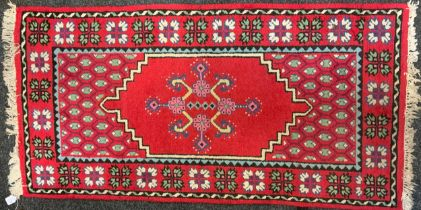 A 20th century Tunisian woolen runner, central geometric medallion within triple border, red ground,