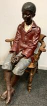 An early 20th century plaster life size model, of a black boy, seated, wearing a red jacket, blue
