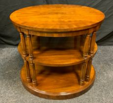 A 20th century, three-tier, mahogany oval centre table/stand, turned and reeded supports, 59cm tall.