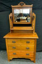 An Arts & Crafts walnut dressing table, central rectangular mirror above a short shelf,