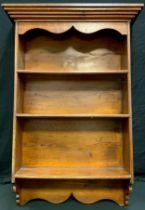 A 20th century oak wall hanging display shelves, outswept cornice above three shelfs. 115cm high,