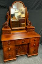 A Victorian Mahogany Dressing Table, the arch-top mirror on carved supports, flanked by two pairs of