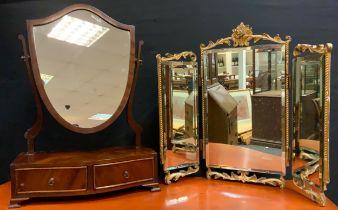 A 20th century, George III style mahogany veneered Toilet Mirror, the shield-shaped mirror on gently