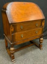 A 20th century oak bureau, arched top, fall front above two long drawers, turned and carved