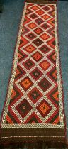 A Persian hand knotted runner, multi coloured geometric lozenge panels, single border, 300cm long,