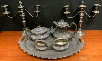 A pair of early 20th century silver plated candelabra; and a silver plated tea, coffee pot, milk jug