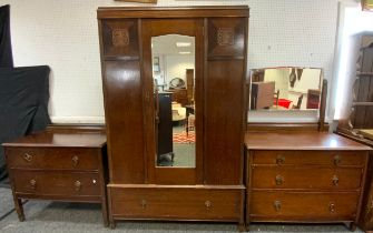 A 20th century oak bedroom suite comprising a double wardrobe with a central bevelled mirrored