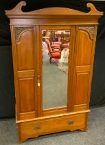 An early 20th Century Mahogany Wardrobe, crested pediment, central door with bevelled mirror, carved