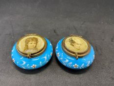 A pair of blue glass enameled pill boxes with glass lids with portraits of young women, A/F - some