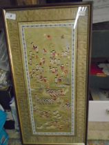 Oriental silk stitchwork of people involved in various activities