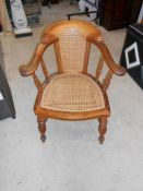 An early 19th century hoop backed Bergere library chair with split cane panel seat