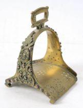 An 18th century brass stirrup: with cast foliate decoration, 18cm high.