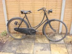 A 1914 Sunbeam lady's bicycle: the black step through frame with shaped bars and bar brakes,